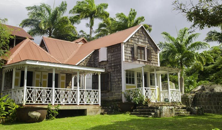 Large Caribbean house with red roof and white verandah at Hermitage Inn Nevis