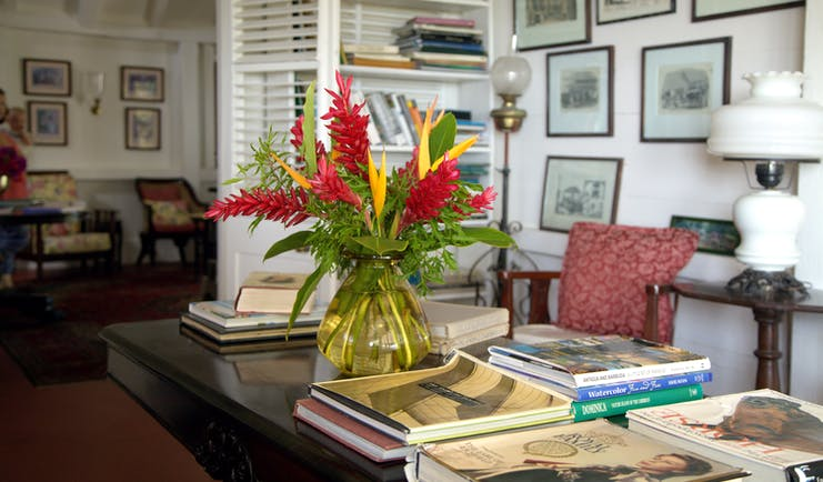Red and yellow heliconia in vase on desk in lounge with books and framed pictures at Hermitage Inn Nevis