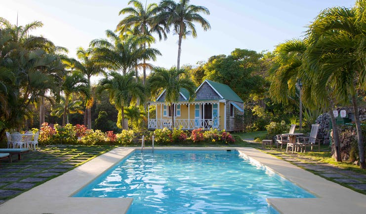 Swimming pool with Caribbean style houses and palm trees at Hermitage Inn Nevis