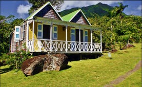 Yellow cottage with white verandah on grassy slope at Hermitage Inn Nevis