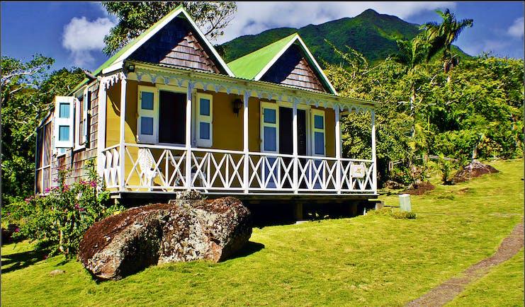 Yellow cottage with white verandah on grassy slope at Hermitage Inn Nevis