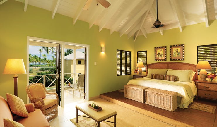 Nisbet Plantation Nevis premier suite bedroom and lounge area leading to balcony with garden views
