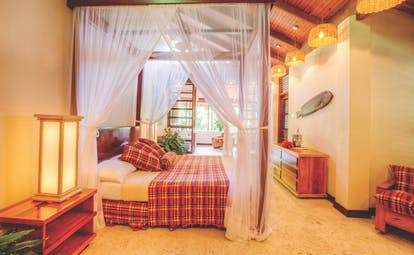 Anse Chastanet St Lucia deluxe beach suite canopied four poster bed lounge area