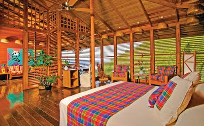 Anse Chastanet St Lucia deluxe hill suite king size bed wooden louvre walls hillside and ocean views