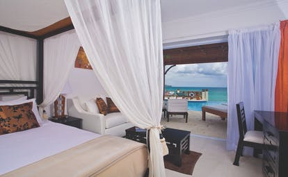 Calabash Cove St Lucia junior suite bed and living area doors opening up to terrace with private rooms
