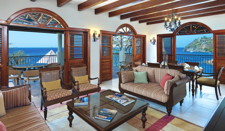 Cap Maison St Lucia suite lounge indoor seating area with sofa and armchairs leading 6o balcony with ocean views