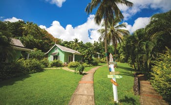 East Winds Inn St Lucia deluxe cottage path across the lawn surrounded by greenery