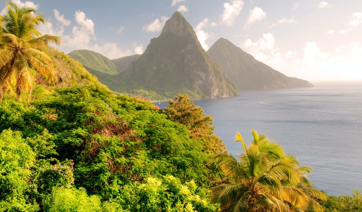 Twin Pitons rock formation in St Lucia, sunset over rocks and ocean