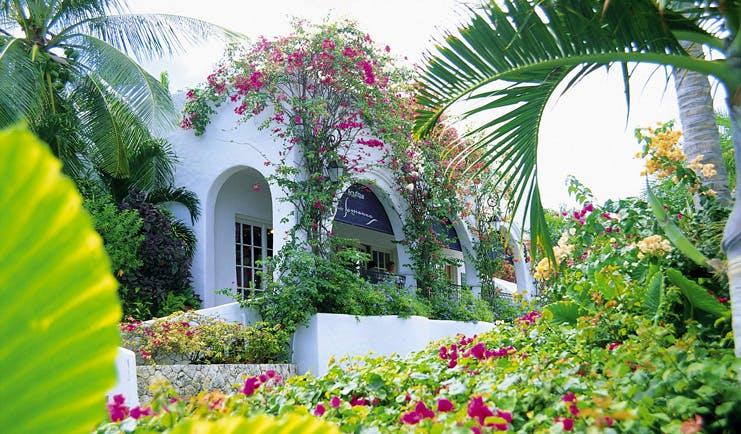 La Samanna St Martin exterior white building archway gardens pink flowers
