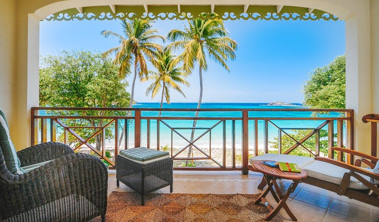 Bequia Beach Hotel balcony, armchair, sun lounger, overlooking beach with white sands and bright blue sea