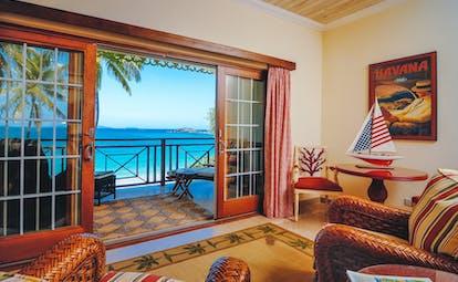 Bequia Beach guestroom balcony, armchairs, bright decor, balcony overlooking beach, white sand, bright blue sea