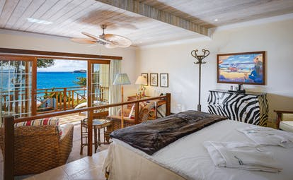 Bequia Beach Hotel guestroom, bed, lounge area, bright decor, balcony overlooking beach