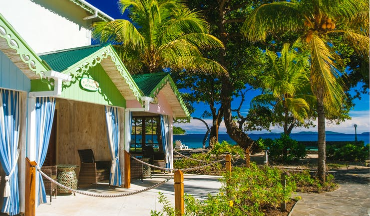 Bequia Beach Hotel pool cabanas, covered shaded outbuildings, brightly painted, palm trees