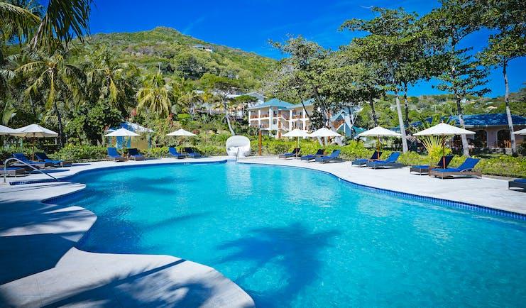 Bequia Beach Hotel pool, sun loungers, umbrellas, greenery
