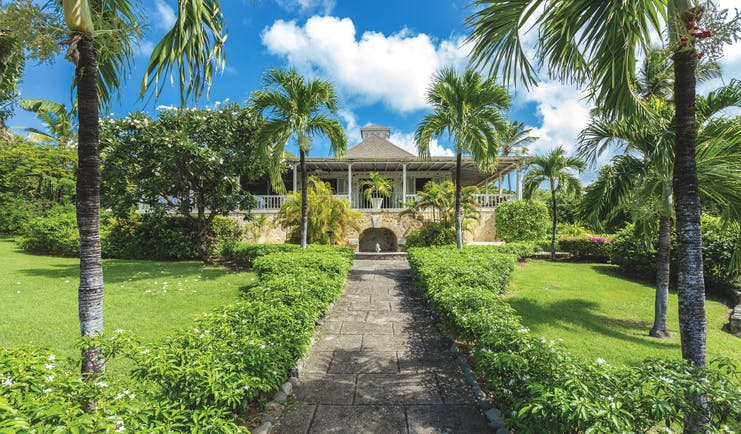 Cotton House St Vincent and the Grenadines path leading up to entrance lawns and palm trees