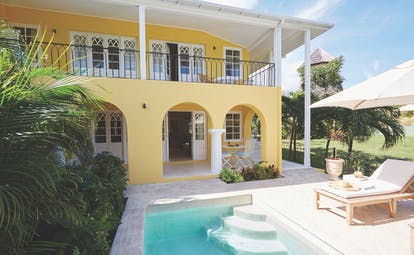 Cotton House St Vincent and the Grenadines villa yellow building pool sun lounger umbrella