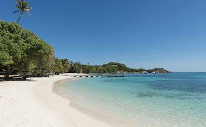 Petit St Vincent beach jetty white sandy beach clear blue ocean