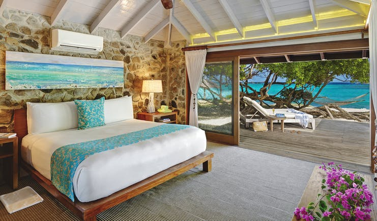 Petit St Vincent beach villa bedroom bed doors leading to decking beach views