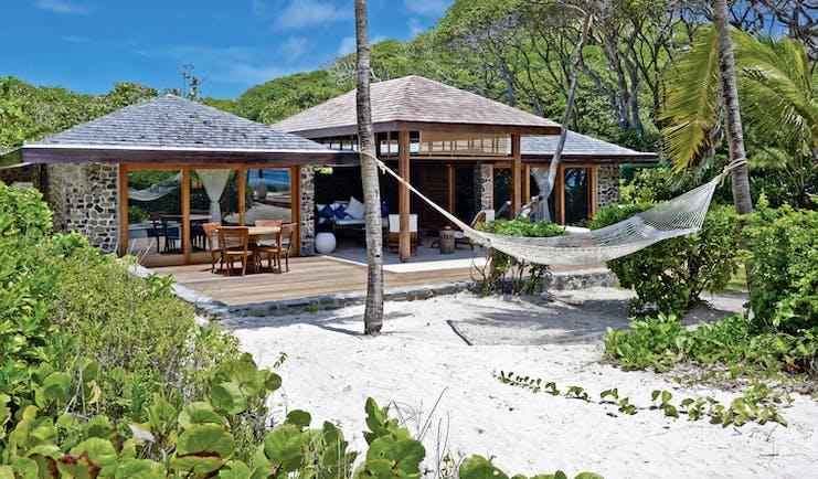 Petit St Vincent beach villa exterior decking out door seating sun loungers hammock