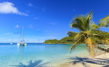 Salt Whistle Bay beach in the Grenadines, white sand, palm tree, boat on the water