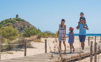 Two adults and two children walking on planks on sandy beach