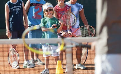 Group of children having tennis lesson