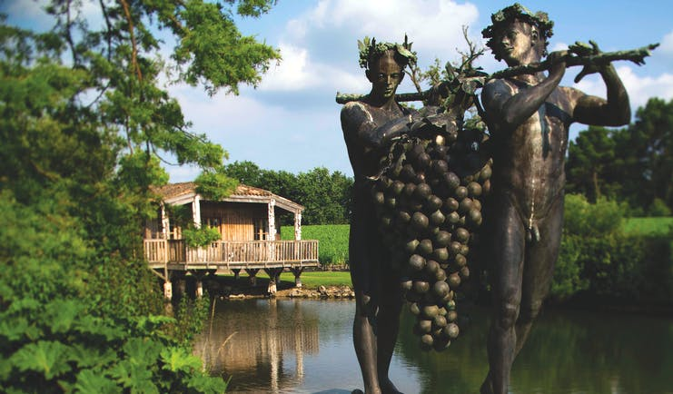 Statue of two people holding bunch of grapes