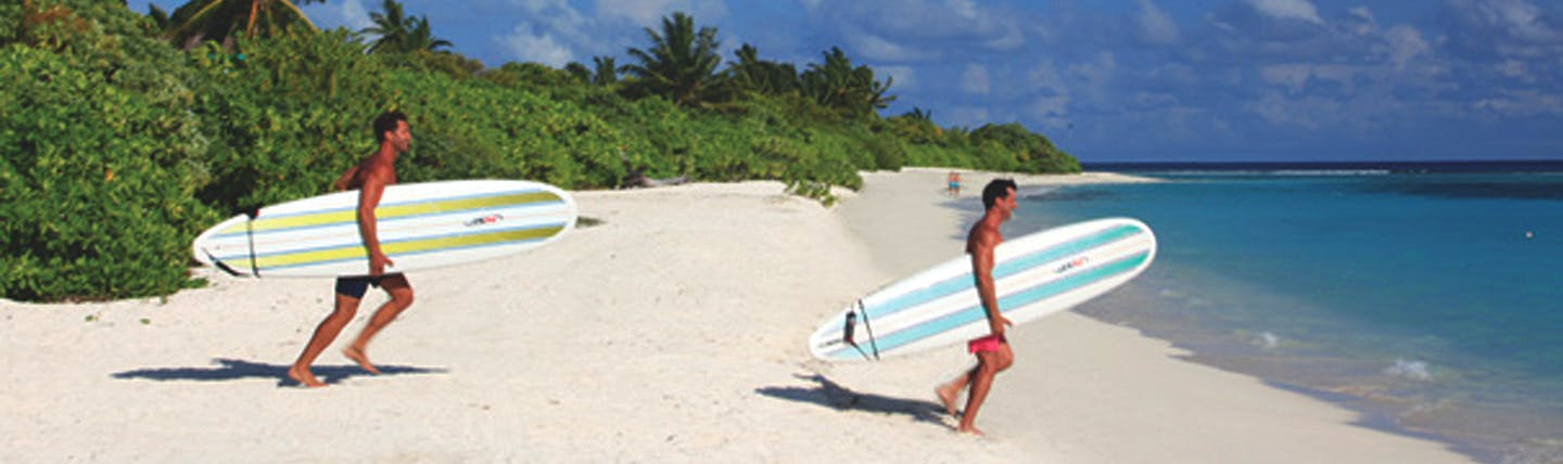 Two men on white sand beach carrying windsurfing boards into the sea