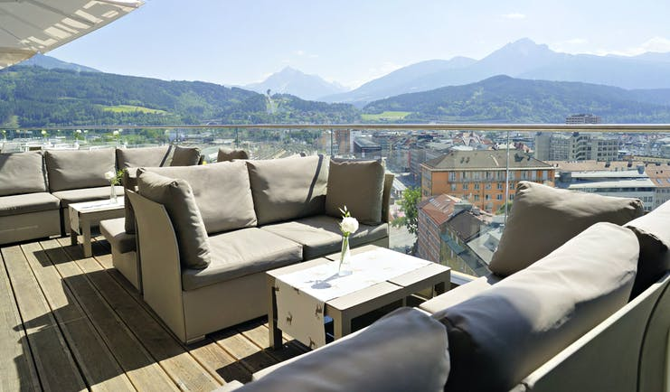 Adlers Hotel Austria outside seating with large sofas and tables on a wooden floor