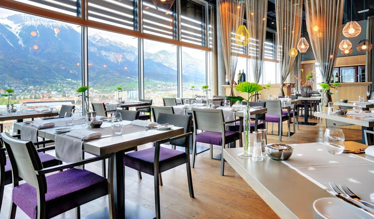 Adlers Hotel Austria Restaurant tables set up for food with large glass windows in the background looking out to mountains in the background