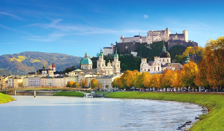 River with domes and buildings with castle on hilltop in Salzburg