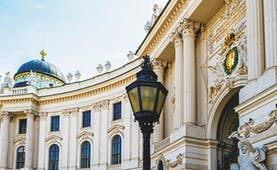 The white stone entrance to the Hofburg palace in Vienna, with arch and lamp