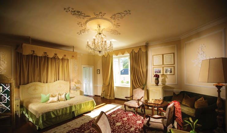 Hotel Bristol Salzburg junior suite with gold, green and red colour scheme with large double bed, sofa, armchairs and chandelier