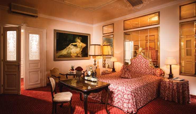 Hotel Bristol Salzburg junior suite with red colour scheme, large mirrors and gold framed paintings