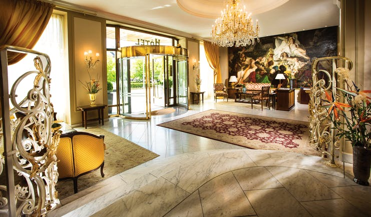 Hotel Bristol Salzburg lobby with grand chandelier, high ceilings, revolving entrance door and rug