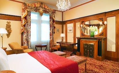 Hotel Bristol Vienna deluxe bedroom cream walls and wood panels armchair and chandelier