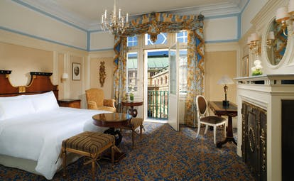 Hotel Bristol Deluxe room with double bed and seating throughout the room and a fireplace in front of the bed