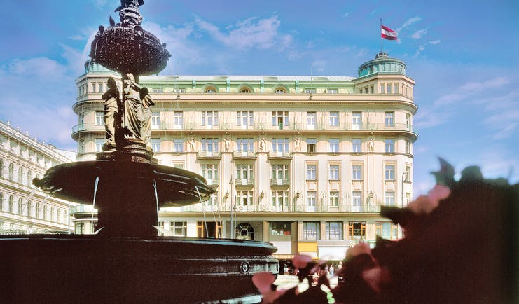 Hotel Bristol Vienna exterior fountain with sculptures of people overlooking large cream building