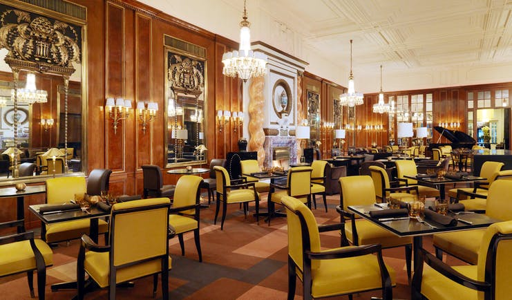 Hotel Bristol lounge, large spacious room occupied by tables for four with chandeliers hanging from the ceiling