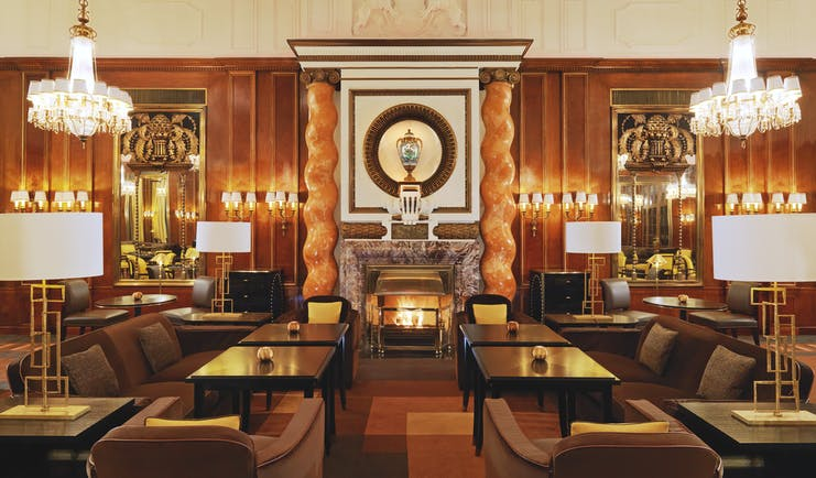 Hotel Bristol Vienna lounge area with several dark wood tables marble columns large fireplace and chandeliers