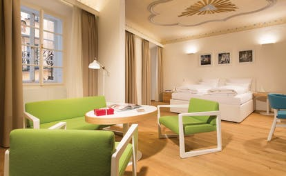 Hotel Goldgasse double bed on one side of a large spacious modern stylised room with a wooden floor and seating around a table