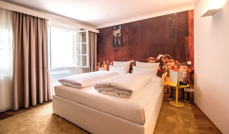Hotel Goldgasse double bed within a spacious room and a red back wall with a light brown floor