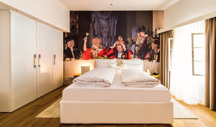 Hotel Goldgasse double bed at the centre of a spacious room on a wooden floor
