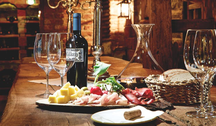 Food and wine laid out on a wooden table