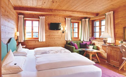 Standard room with wood pannelled ceiling, walls and floors with double bed and small windows
