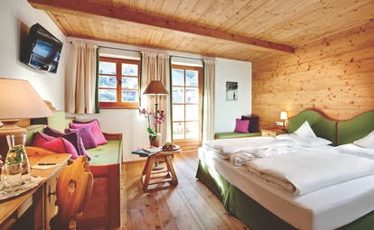 Standard suite with wood pannelled ceiling and floor and wooden window opening onto a balcony