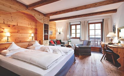 Superior room with wood pannelled walls and floor, large double bed and large windows