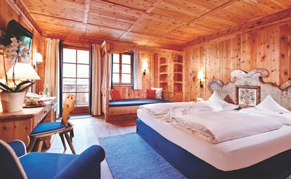 Superior suite with wood pannelled ceiling, floor and walls, with large double bed and large windows
