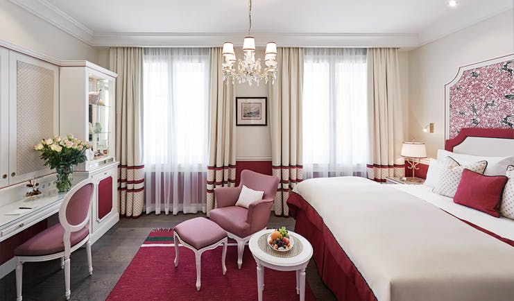 Hotel Sacher deluxe room, bed with pink and red details, vanity table, pink armchair
