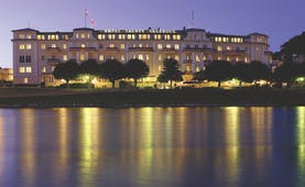 Hotel Sacher hotel exterior, grand style building at twilight, lit up, overlooking river
